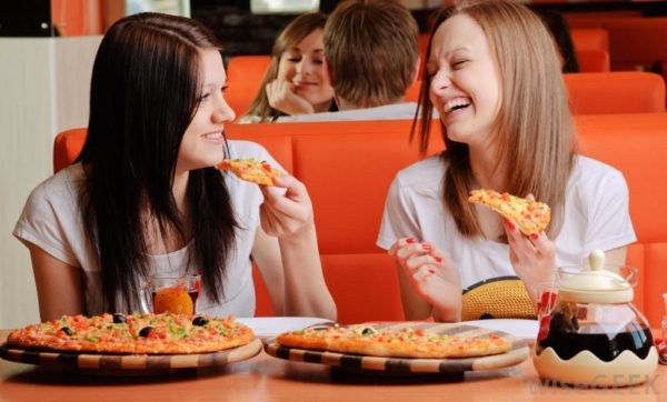 two women eating pizza at booth